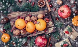Carte de Noël Les cadeaux de Noël, grenade, mandarines, écrous, graines de cacao, sapin s'embranche sur le fond neigeux en bois photo libre de droits