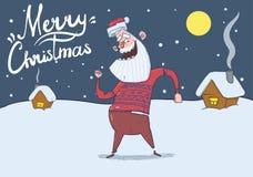 Carte de Noël de Santa Claus de sourire dans la danse de chandail de cerfs communs pendant la nuit neigeuse devant les maisons de Photos stock