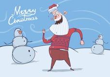 Carte de Noël de Santa Claus de sourire drôle dans la danse de chandail de cerfs communs à côté des bonhommes de neige par temps  Photographie stock