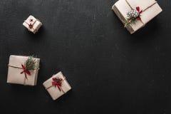 Carte de Noël Sur le fond noir, les cadeaux décoratifs ont arrangé dans le coin avec l'espace pour un message de salutation pour  Photo libre de droits