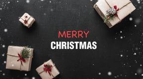 Carte de Noël Sur le fond noir, les cadeaux décoratifs ont arrangé dans les coins avec un message de Noël au centre du Photo libre de droits