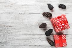 Carte de nouvelle année, cadeau enveloppé dans l'emballage rouge avec les cônes décoratifs colorés de pin Photos stock