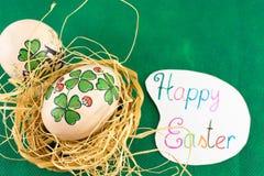 Carte de Pâques heureuse avec les oeufs de pâques décorés Photographie stock