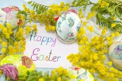 Carte de Pâques heureuse entourée avec les oeufs et la mimosa Photographie stock
