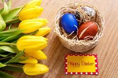 Carte de Pâques heureuse et tulipes jaunes Image stock