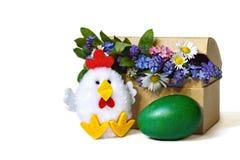 Carte de Pâques heureuse : Oeuf de pâques, fleurs vertes de ressort et jouet de poulet d'isolement Photographie stock