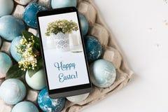 Carte de Pâques mobile sur l'écran, oeufs décoratifs sur le bleu Image stock
