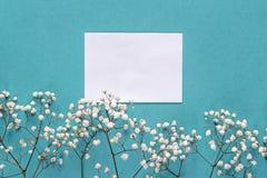 Carte de papier blanc avec de petites fleurs blanches sur le fond bleu pour Photo libre de droits