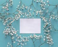 Carte de papier blanc avec de petites fleurs blanches sur le fond bleu pour Photographie stock