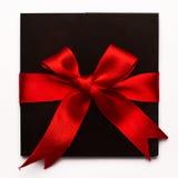 Carte de papier noire avec le ruban rouge de textile d'isolement sur le blanc Image stock