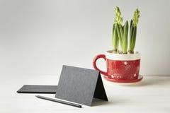 Carte de papier ou carte postale noire sur la table en bois blanche, l'espace pour la disposition Fleurs dans le pot rouge Photographie stock libre de droits