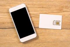 Carte de Smartphone et de SIM sur la table de bureau, vue supérieure Photo libre de droits