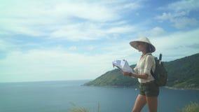 Carte de touristes femelle de lecture en haut de la colline banque de vidéos