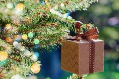 Carte de vacances de Noël et de nouvelle année Boîte-cadeau accrochant sur la branche d'arbre de Noël sur le fond de vert bleu photos libres de droits