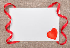 Carte de Valentine avec dessiner le coeur rouge sur la toile de jute Images stock