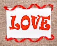 Carte de Valentine avec l'amour et le ruban de mot de dessin Images stock