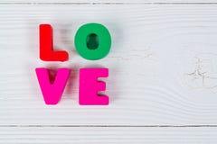 Carte de Valentine avec le texte d'amour sur le fond et la cannette de fil en bois blancs Photographie stock libre de droits