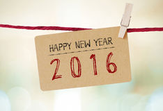 Carte de vintage avec le mot de la bonne année 2016 accrochant sur l'habillement Photo libre de droits
