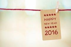 Carte de vintage avec le mot de la bonne année 2016 accrochant sur l'habillement Photographie stock