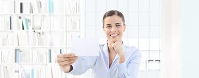 Carte de visite professionnelle de visite de sourire d'apparence de femme dans sa main sur l'offi intérieur Photo libre de droits