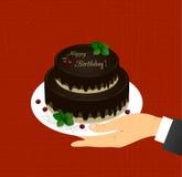 Carte de voeux avec l'image du gâteau de chocolat à deux niveaux avec les mots joyeux anniversaire et cerises dans une main Photo stock