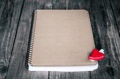 Carte de voeux avec le bloc-notes et coeur rouge sur le fond en bois Images libres de droits