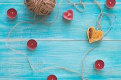 Carte de voeux avec le fond minable en bois bleu avec le coeur, les bougies et un écheveau de fil Foyer sélectif peu profond Images stock