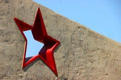 Carte de voeux avec le jour du défenseur de la patrie 23 février étoile cinq-aiguë rouge dans un mur en béton contre un bleu Photographie stock libre de droits