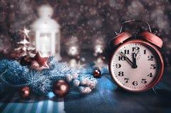 Carte de voeux avec le réveil montrant cinq à douze et disposition d'hiver Images stock
