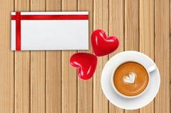 Carte de voeux avec le ruban rouge, le café et deux coeurs rouges Photos stock