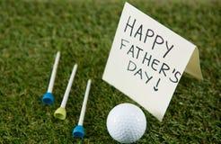Carte de voeux avec le texte heureux de jour de pères par la boule de golf et pièces en t sur le champ Images stock