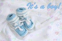 Carte de voeux : butins nouveau-nés tricotés de bébé sur le fond blanc couvrant à crochet avec les coeurs colorés Photos libres de droits