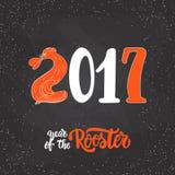 Carte de voeux de calligraphie de lettrage de Noël et de nouvelle année avec 2017 ans du coq du feu rouge sur le noir Photo stock