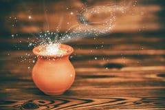 Carte de voeux de concept de pot d'argile avec la lumière mystique de miracle dessus Images stock