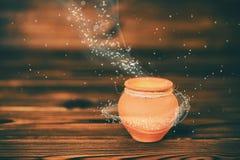 Carte de voeux de concept de pot en céramique avec la lumière mystique de miracle Photos stock