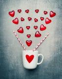 Carte de voeux de jour d'amour et de valentines avec la tasse et les coeurs rouges Images stock
