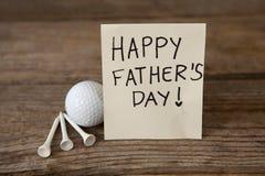 Carte de voeux de jour de pères avec la boule de golf sur la table Photos libres de droits