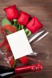 Carte de voeux de jour de valentines, champagne et roses rouges Photos stock