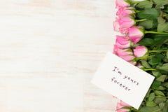 Carte de voeux de jour du ` s de Valentine avec les fleurs roses au-dessus du dos en bois Images libres de droits