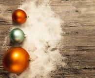 Carte de voeux de Noël avec des boules de Noël et neige sur un fond en bois Images stock