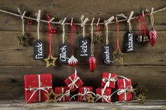 Carte de voeux de Noël avec des présents de rouge et de bons souhaits à Ger Photos stock