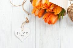 Carte de voeux de ressort avec les tulipes oranges, coeur en bois Images stock