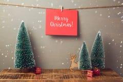 Carte de voeux de vacances de Joyeux Noël remettant sur le mur avec le pin Photo stock
