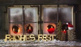 Carte de voeux en bois de Noël avec le texte allemand et les bougies rouges : Merr Photos stock
