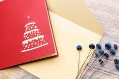 Carte de voeux, enveloppe et fleurs rouges sur un plan rapproché en bois léger de fond Images libres de droits