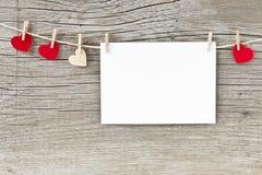 Carte de voeux et coeurs de jour de valentines accrochant sur une corde Images stock