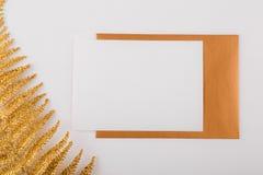 Carte de voeux et enveloppe blanches de maquette avec les feuilles de fougère d'or et le fond clair photos stock