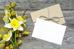 Carte de voeux et enveloppe blanches vides avec des fleurs de jonquille et photos libres de droits