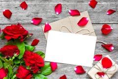 Carte de voeux et enveloppe blanches vides avec des fleurs, des pétales et le boîte-cadeau de roses rouges Photos libres de droits