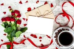 Carte de voeux et enveloppe blanches vides avec la tasse de café et les roses rouges Images libres de droits